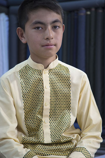 Picture of Afghani people (Afghanistan): Boy in shalwar-kameez in clothing store in Mazar-e-Sharif
