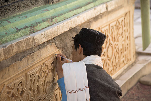 Man scribbling something on the marble at the base of the tomb of Ansari | Gazar Gah | 阿富汗