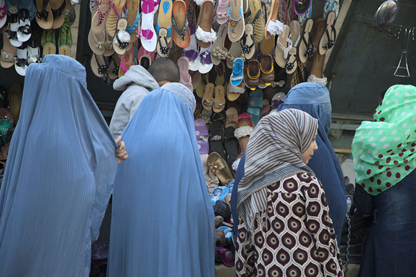 Women examining shoes at a shoe stall in the bazaar of Mazar | Mazar-e-Sharif Bazaar | Afghanistán