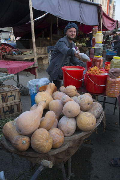 Man at a pumpkin stall in the bazaar of Mazar-e-Sharif | Mazar-e-Sharif Bazaar | Afghanistán