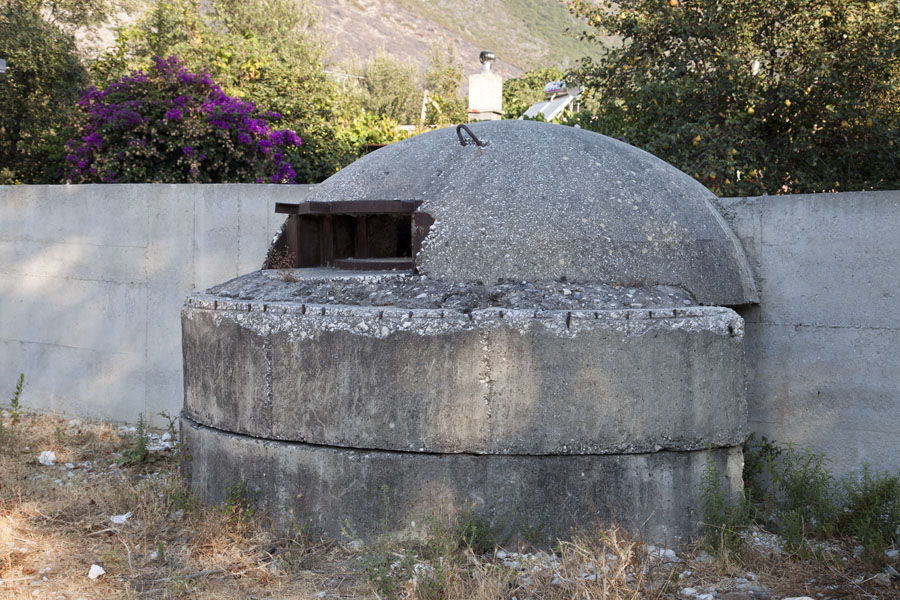 Picture of Bunker of the Hoxha regime integrated into the wall around a house
