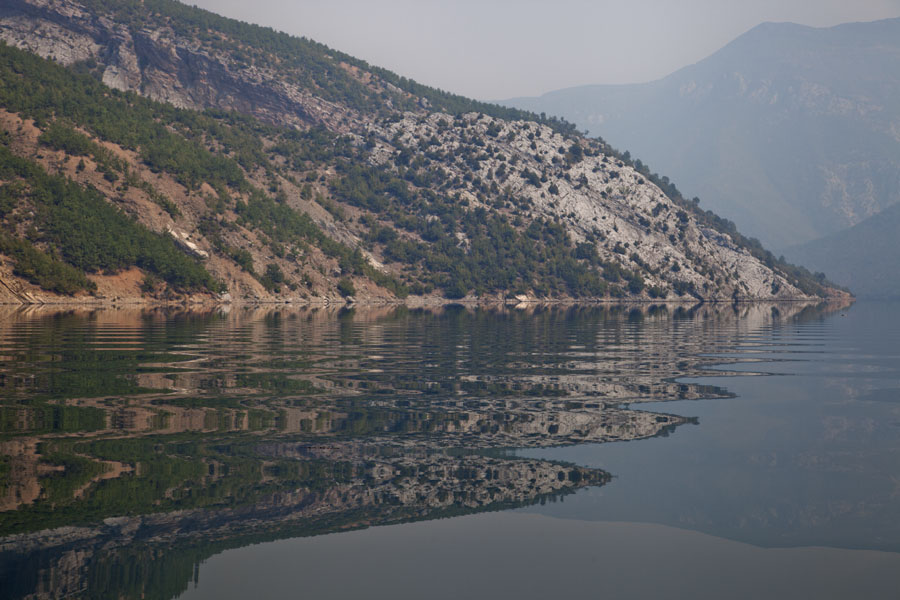 Foto van View of Lake Koman with reflection of mountains in the waves - Albanië