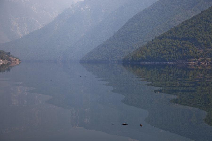 Mountains mirrored in the water of Lake Koman | Koman to Fierze boat | Albanië