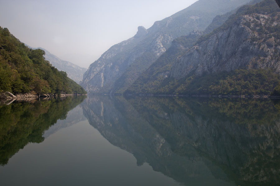 Tranquil waters of Lake Koman reflecting the mountains | Koman to Fierze boat | Albanië