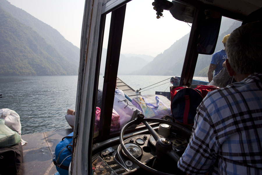 Driver steering the bus-boat through over the lake with a regular bus steering wheel | Koman to Fierze boat | Albanië