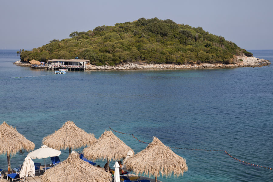 One of the islands off the coast of Ksamil with parasols in the foreground | Ksamil beaches | Albania