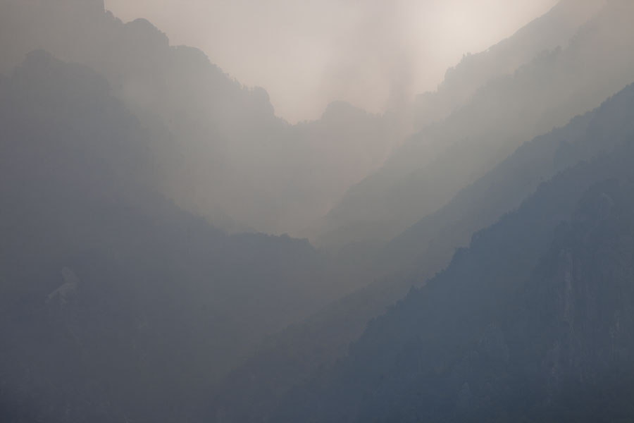 Picture of Theth (Albania): Valley filling with smoke giving the mountain ranges a misty appearance