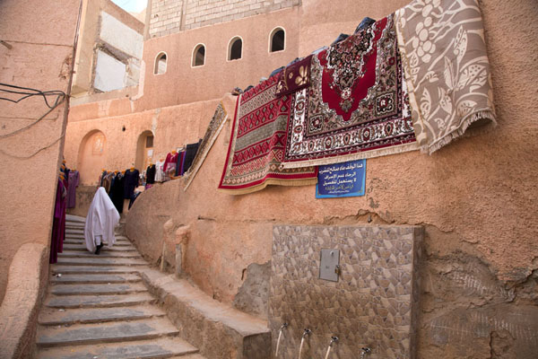 Woman walking up stairs with carpets in the old town of El Atteuf | El Atteuf | Algeria