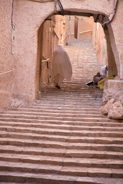 Foto de Woman dressed in white walking up the stairs in the old town of Ghardaïa - Argelia - Africa
