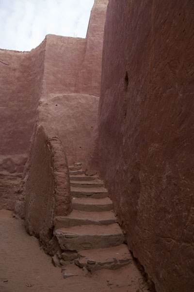 Curved walls and stairs in a sandy street of the old town of Timimoun | Vielle ville de Timimoun | Algérie
