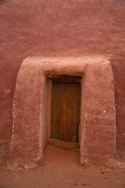 Red-painted adobe house with wooden door | Vielle ville de Timimoun | Algérie