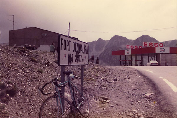 Bike parked against the old marker of Envalira mountain pass | Port d'Envalira | Andorra