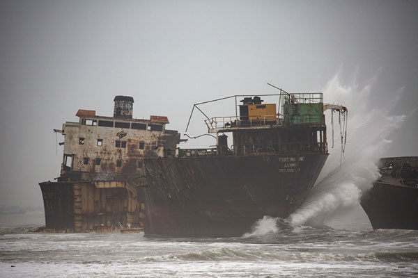 Wave slamming into a large ship in the surf | Playa de buques naufragados | Angola