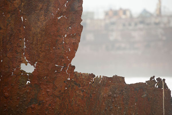 Looking past a rusty wall of a ship with another shipwreck in the background | Playa de buques naufragados | Angola