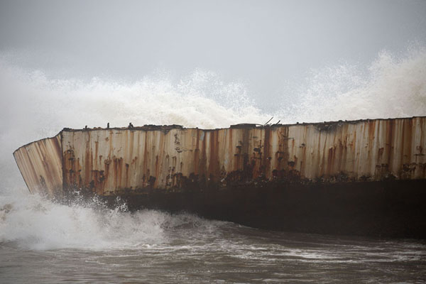 Wave slamming against a smaller shipwreck | Playa de buques naufragados | Angola