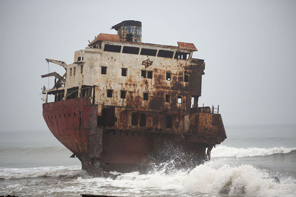 The rear part iof a shipwreck engulfed by waves | Scheepswrakken strand | Angola