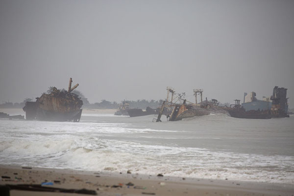 Looking south over the beach with several shipwrecks in the surf | Shipwreck beach | Angola