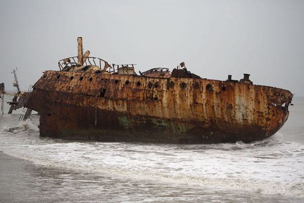 Foto van The rusting hull of the Karl Marx, one of the many shipwrecks on the beachCacuaco - Angola