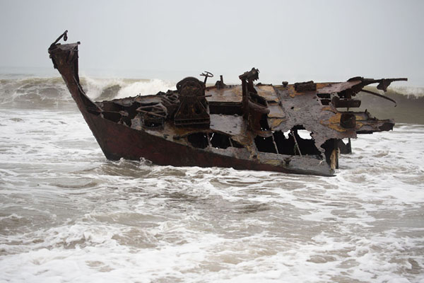 Bow of a boat rusting away in the surf | Scheepswrakken strand | Angola