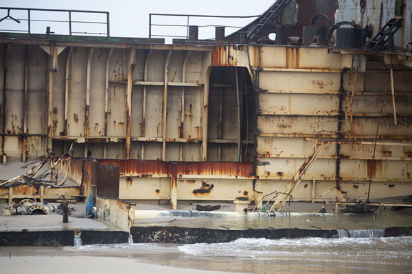 Part of the open remains of a ship resting on the beach | Scheepswrakken strand | Angola