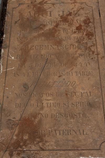 Picture of Alto das Cruzes cemetery (Angola): Close-up of old tombstone with red sand at the cemetery of Alto das Cruzes