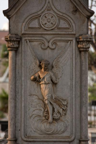Picture of Alto das Cruzes cemetery (Angola): Sculpted angel catching late afternoon sunlight on a tombstone in the cemetery of Alto das Cruzes