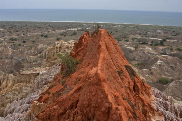 Red hill protruding from the cliffs with the Atlantic Ocean in the background | Miradouro da Lua | Angola