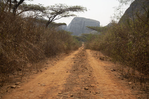 Dirt track with rock formation in the distance | Pungo Andongo | Angola