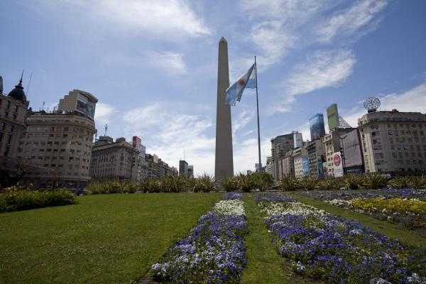 Obelisk and flag with flowers in the foreground are the centerpiece of the Avenida 9 de Julio | Buenos Aires | Argentinië