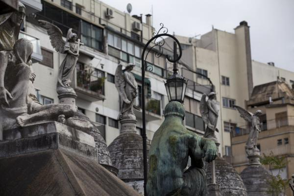 Picture of La Recoleta Cemetery (Argentina): Row of statues on tombs with buildings surrounding La Recoleta in the background