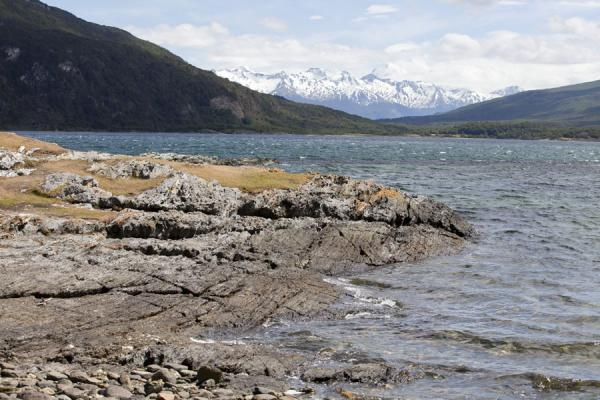 Rocky shoreline with snow-capped mountains in the background | Tierra del Fuego National Park | Argentina