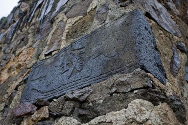 Khachkar of person with shoes and hat incorporated in the wall of the belltower of the Monastery of St. John | Ardvi | Armenia