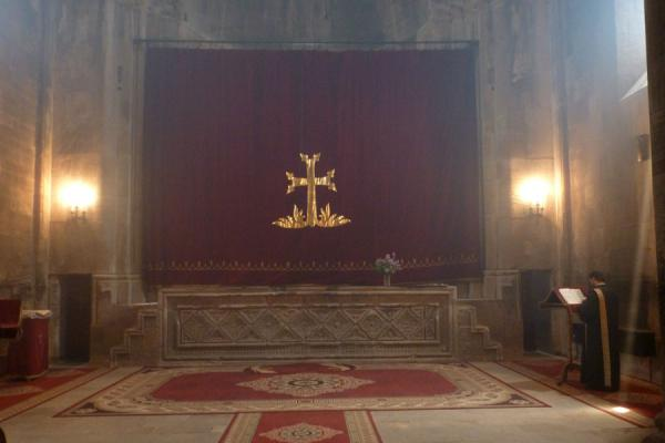 Picture of Gandzasar Monastery (Armenia): Cross-covered curtain hiding the altar of Cathedral of St. John the Baptist with chanting priest