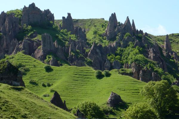 Green fields with volcanic pinnacles pointing at the sky | Goris cave dwellings | Armenia