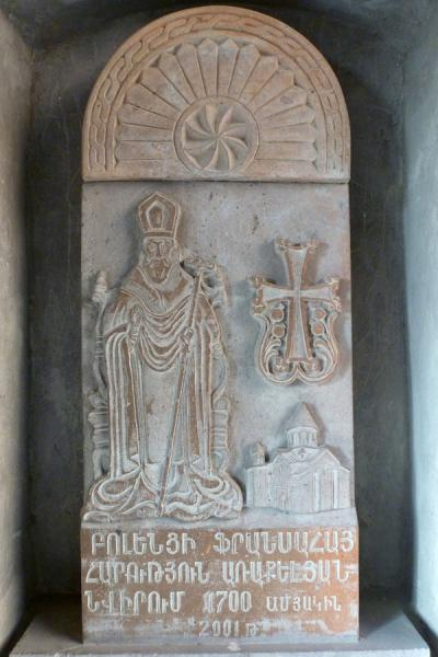 Saint and cross with model of Astvatsatsin church carved out in stone | Khor Virap Monastery | Armenia