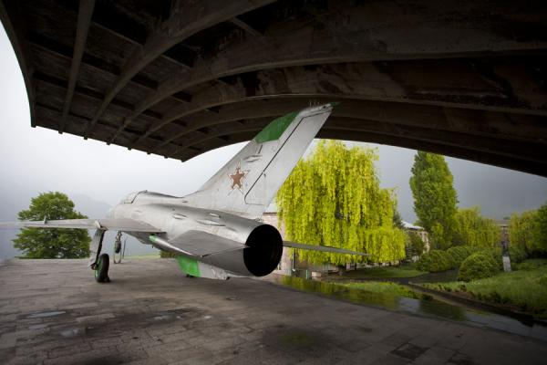 The MiG-21 under its shelter with trees and grey sky in the background | Mikoyan museum | Armenia