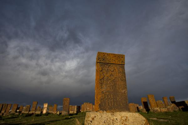 Foto van Dark sky looming over the khachkars of Noratus at the end of the day - Armenië - Azië