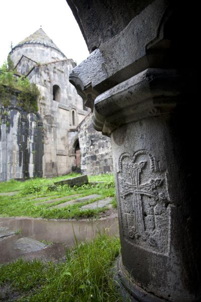 Column of the library with carved cross and the Mother of God Church in the background | Sanahin Monastery | Armenia