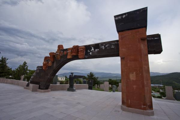 Modern arch with sculpted heads is part of the memorial complex | Stepanakert Memorial Complex | Armenia