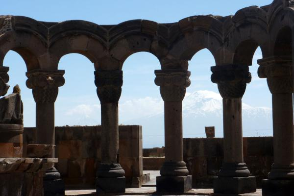 Arches supported by columns with snow-capped mountains in the background | Cathedral de Zvartnots | Armenia