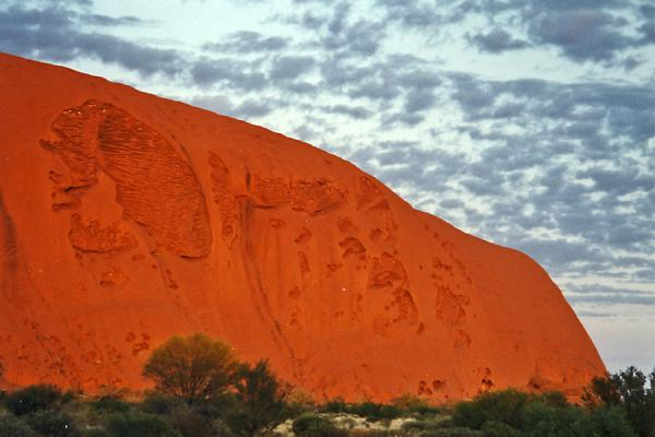 Foto de Sunset leaves anyone in amazement - the Rock is getting coloured deeper and deeper red, until it disappears in the night.Ayers Rock - Australia