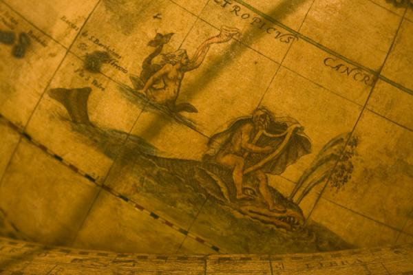 Human figures riding fishes and whales on a globe | Globe museum | Austria