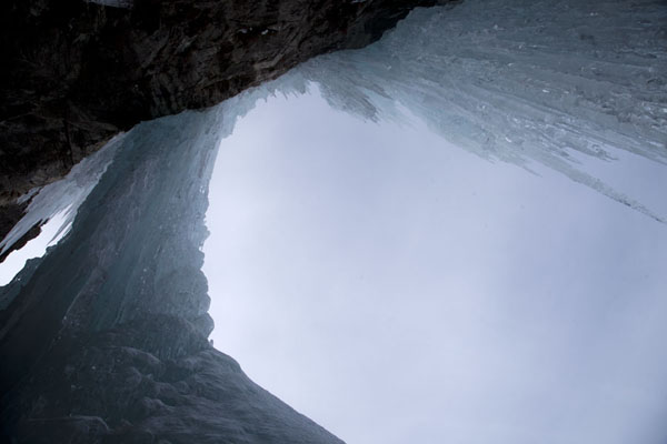Looking up frozen waterfalls from within a cave | Arrampicare sul ghiaccio in Tirol | Austria