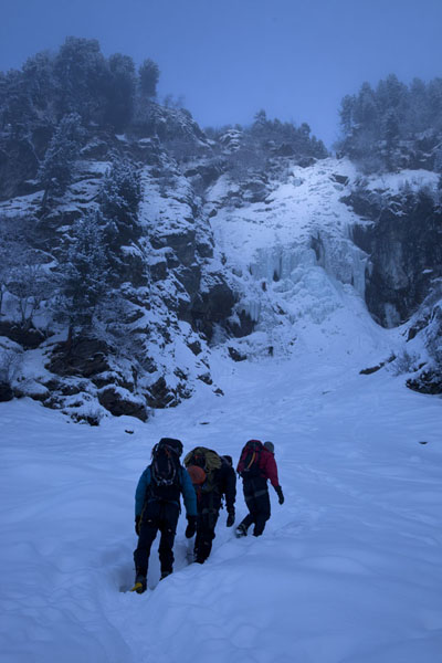 Walking through the snow on the way to a frozen waterfall | Escalade sur glace à Tirol | l'Autriche