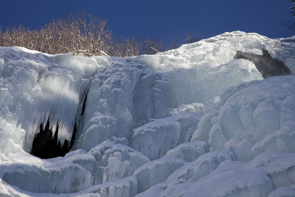 Picture of Frozen waterfall emitting blue light on a sunny day