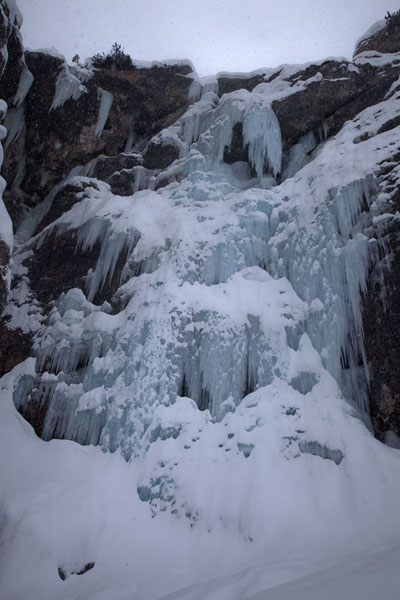 Frozen waterfalls covered in snow tumbling down a rocky cliff | Arrampicare sul ghiaccio in Tirol | Austria