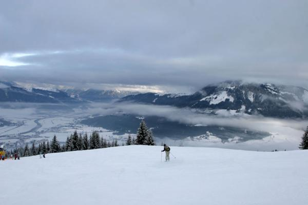 Skiing the slopes of St. Johann with a view of the cloudy valleys | St. Johann Skiing | Austria
