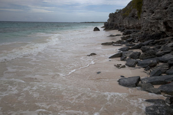 A narrow stretch of pink-sand beach with rocks south of Greenwood | Columbus Point | Bahamas