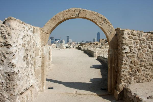 Picture of Assyrian arch in the Bahrain Fort with the modern skyline of Manana