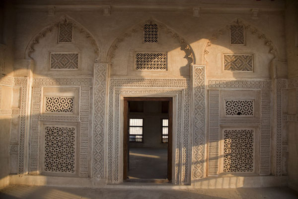 Light falling on a richly decorated wall with door in a room on the second floor | Bait Sheikh Isa bin Ali | Bahrain